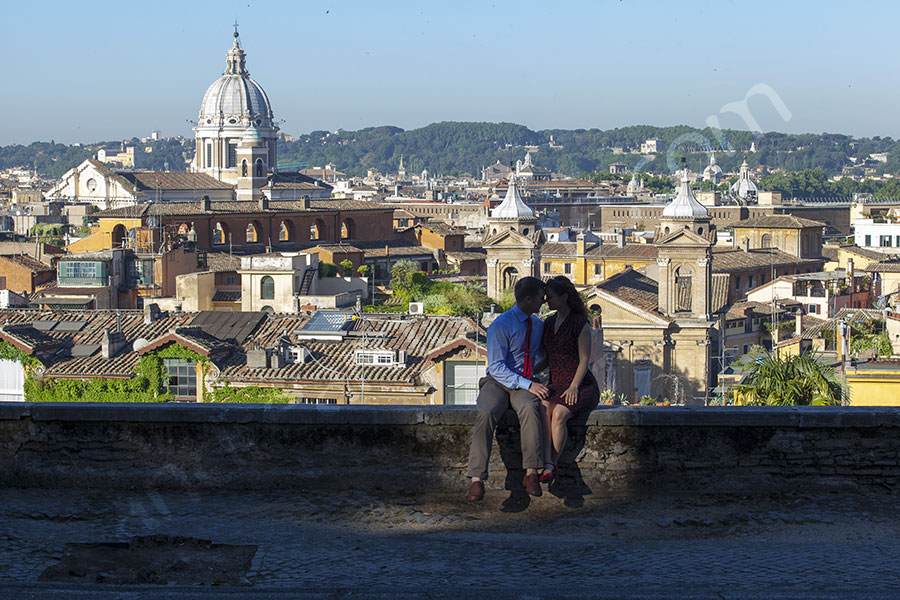 Romantic kiss on the ledge between Trinita' dei Monti and Parco del Pincio. Engagement photos in Rome.