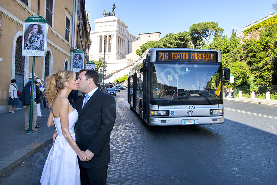 Couple kissing in love in front of a bus Teatro Marcello