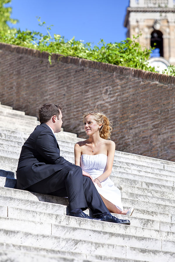 Bride and groom sitting down on stairs by the Capidoglio piazza