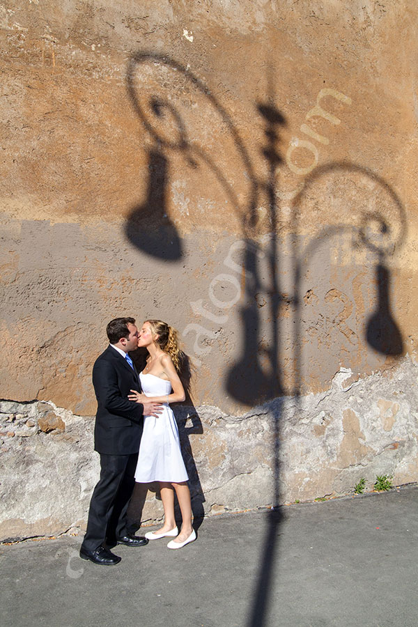 Newlyweds kissing next to the shadow of a light pole onto the street wall