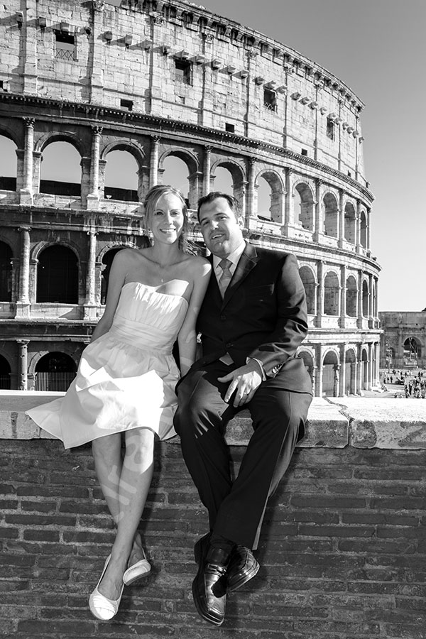 The Coliseum. Man and woman in matrimonial attire sitting on a wall.