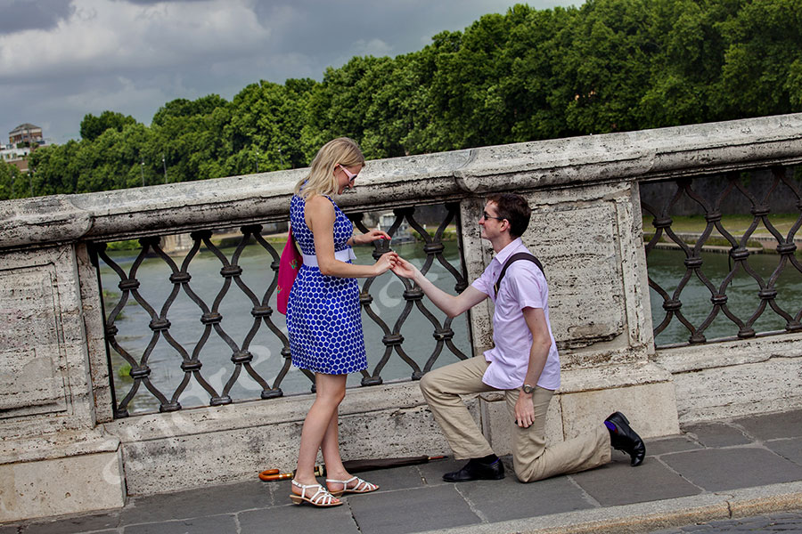 The secret proposal asked on Castel Sant'Angelo bridge. Surprise wedding proposal photography in Rome.
