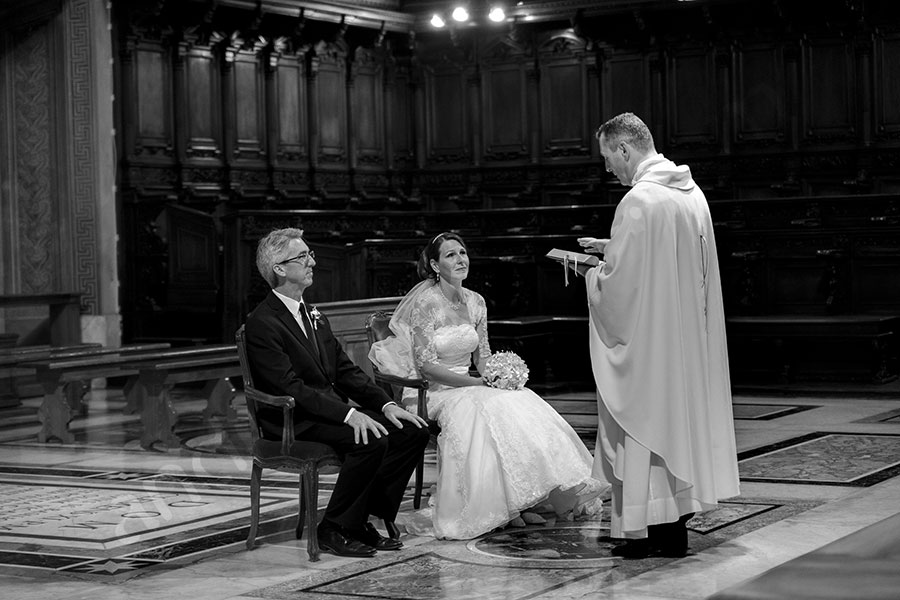 Close up black and white picture showing the bride and groom renewing their vows. Wedding vow renewal ceremony.