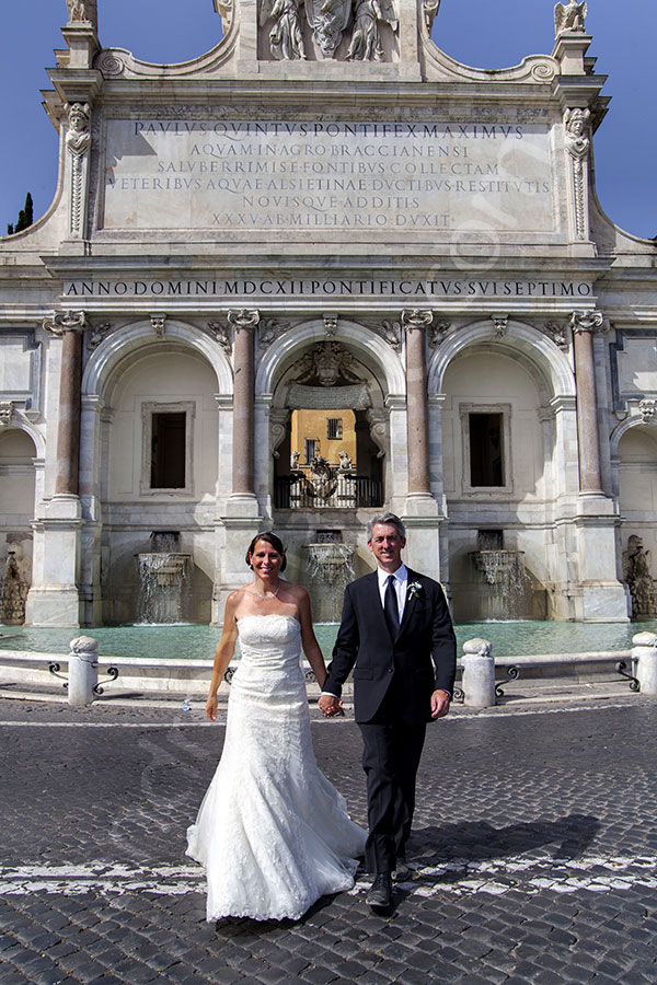 Wedding couple walking in front of the Gianicolo water fountain in Rome