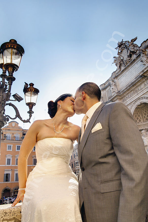 Photo session including a wedding couple kissing by the Trevi fountain.