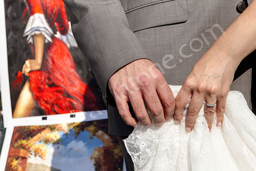 The young couple rings photographed while holding the dress