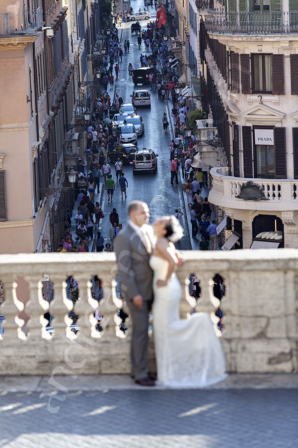 Couple pat the balcony of the Spanish steps overlooking Via del Corso