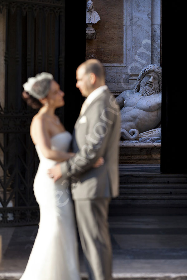 Newlyweds kissing in front of the Campidoglio statue.