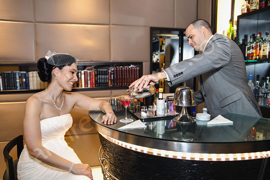 The groom bartender preparing a drink for the bride behind a bar