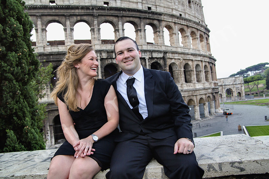 On a beautiful engagement style session. Sitting on a marble wall. Coliseum. Honeymoon Photographer Rome.