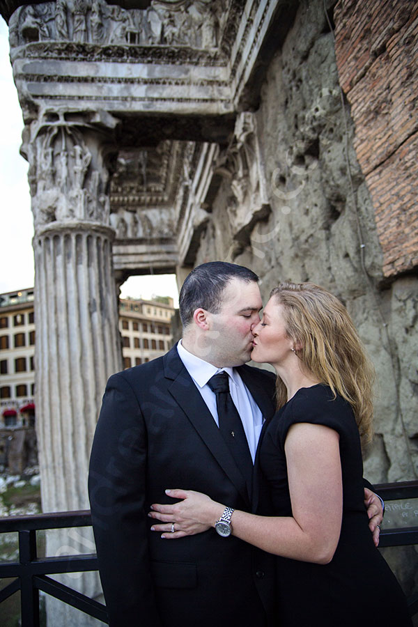 Couple kissing underneath roman ruins in Rome
