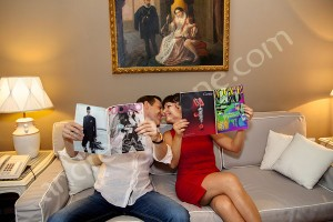 Couple kissing while holding and reading fashion magazine