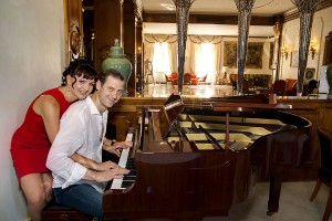 Couple playing the piano together inside Hotel Androvandi in Rome Italy
