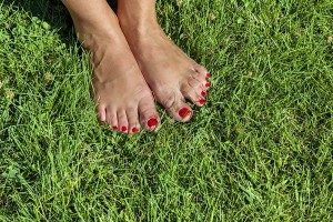 Female feet on the grass with red finger nails