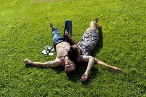 Couple relaxing on green grass Villa Borghese Rome Italy