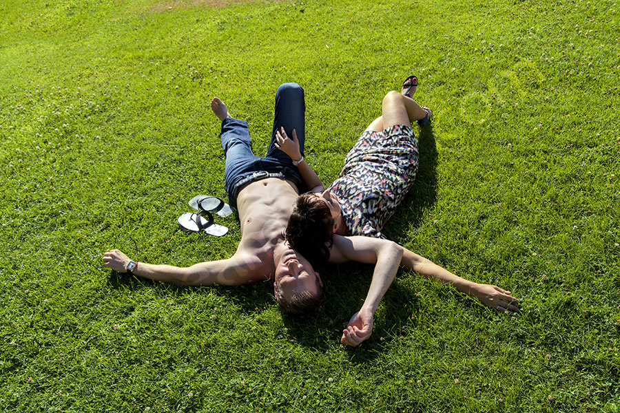 Couple relaxing on green grass Villa Borghese Rome Italy. Photographer.