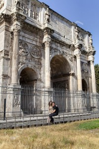 Couple posing during a photographer session underneath Constantine's Arch in Rome