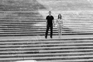 Black and white image of a couple standing on the steps of Piazza del Campidoglio in Rome