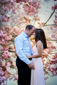 Couple photographed in front of pink flower trees in Rome