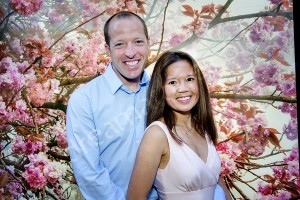 Couple posing together in front of pink flowery trees