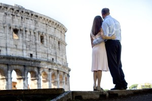 Couple looking at the Roman Colosseum in Rome photographed from the back