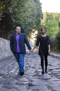 Walking together holding hands on the ancient Appia road in downtown Rome
