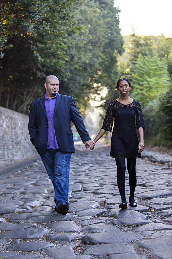Walking together holding hands on the ancient Appia road in downtown Italy