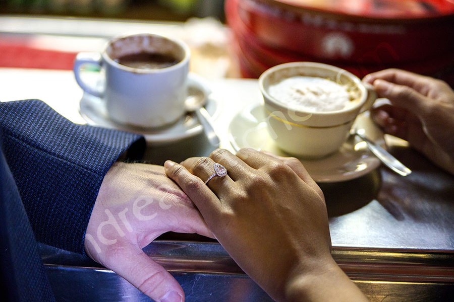 Engagement ring during a coffee break holding hand together.