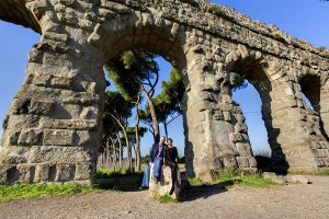 Engagement couple photographed underneath huge roman aqueduct in Rome Italy Parco Appio Claudio