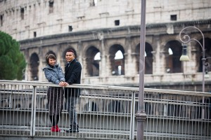 Young couple together standing on a bridge in front of the Roman Coliseum in Rome Italy