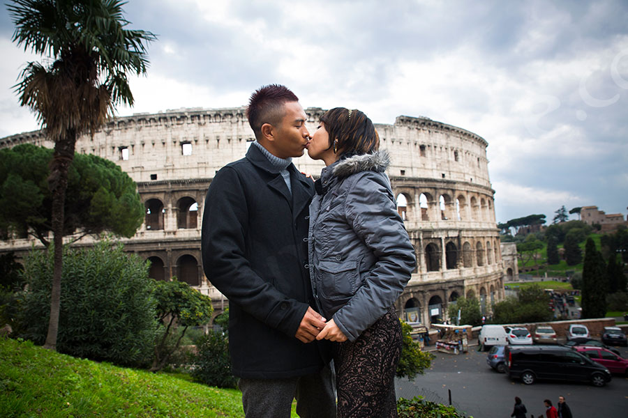 Kissing in front of the Colosseum in the city center.