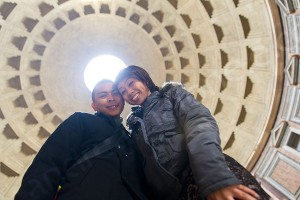 Couple standing underneath the hole in the ceiling of the roman Pantheon in Rome