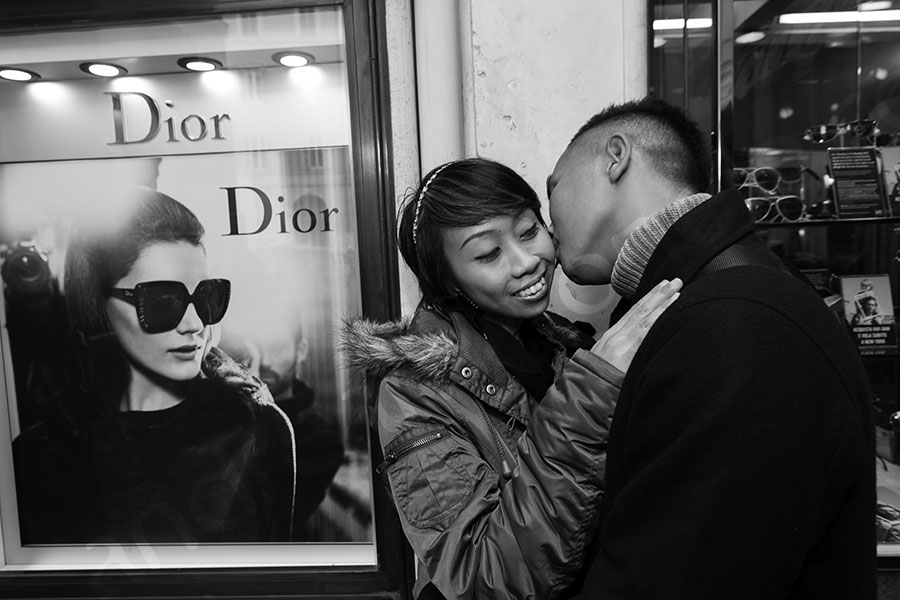 Picture of a couple having fun next to a Dior showcase