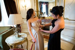 Bride helping bridesmaid with her dress during the wedding preparation in Rome