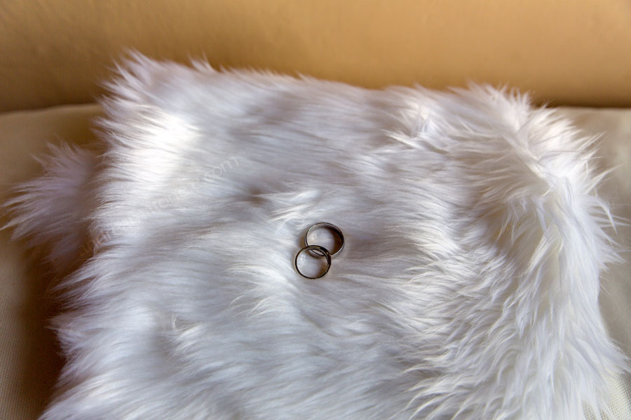 Matrimonial rings photographed on a soft furry white cushion