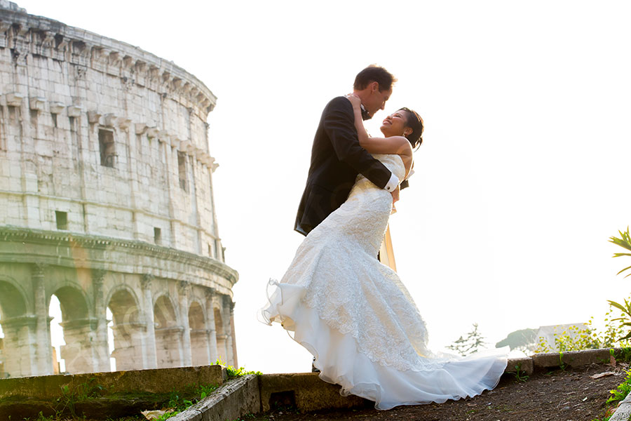 Bride and groom together the roman Colosseum in Rome