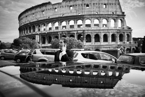Groom talking on the phone outside the Roman Colosseum