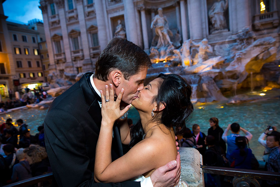 Couple just married kissing at the Trevi fountain evening time