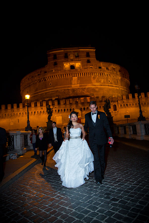 Just married couple walking on Ponte Castel Sant'Angelo in Rome Italy