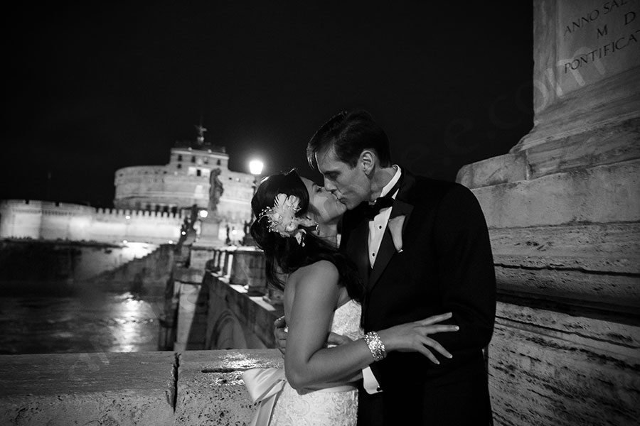 Matrimonial couple kissing Castel Santangelo bride in Rome Italy