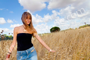 Model walking in a field in Italy after a makeup session