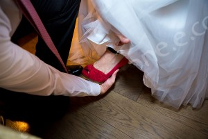 Groom putting on the shoes of the bride