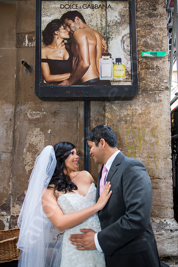 Couple posing in front of a street poster in the Italian streets.