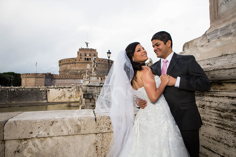 Castel Sant'Angelo with the bride and groom posing in front of the exterior facade.