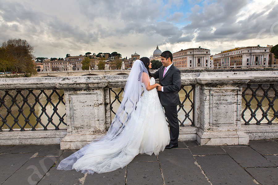 Castel Ponte Sant'Angelo. Full view of bride and groom in their matrimony attire.