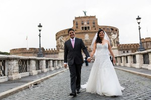 Wedding couple walking hand in hand on Castel Sant'Angelo bridge in Rome Italy