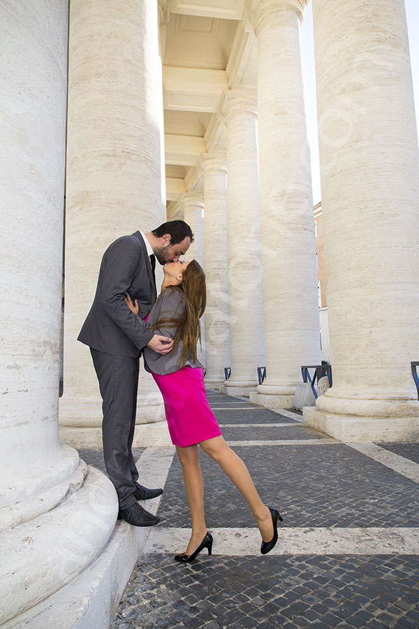 Romance at underneath the colonnade of Saint Peter's in the Vatican. Engagement photographer Rome