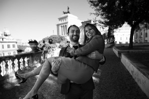 He carries her in his arms with Piazza Venezia photographed in the distance