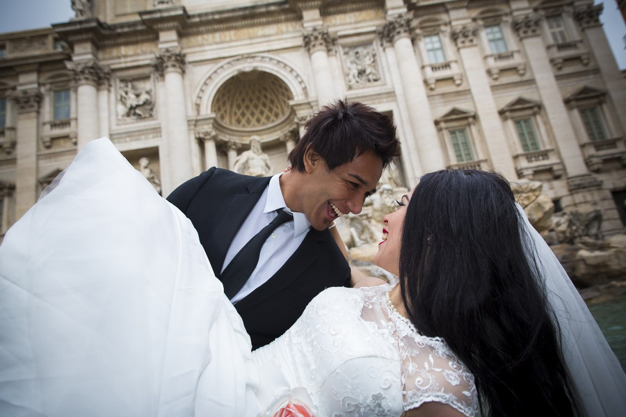 Groom picks up the bride at the Trevi fountain. Romantically in love.