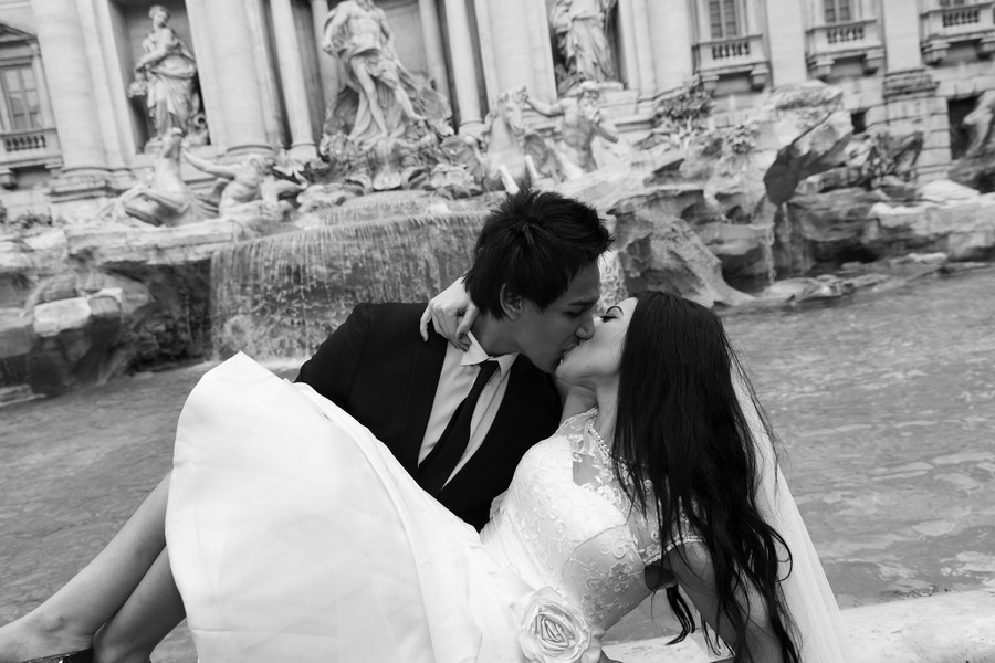 Bride and groom kissing at the Trevi fountain in black and white version